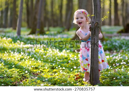 Adorable laughing child, blonde healthy toddler girl enjoying nature, playing, hiking and hiding behind the trees in spring forest with snowdrops flowers - stock photo