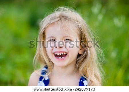 Adorable laughing little girl with long blond curly hair, outdoor portrait in summer park on bright sunny day. Smiling child in green grass field. Closeup portrait. - stock photo
