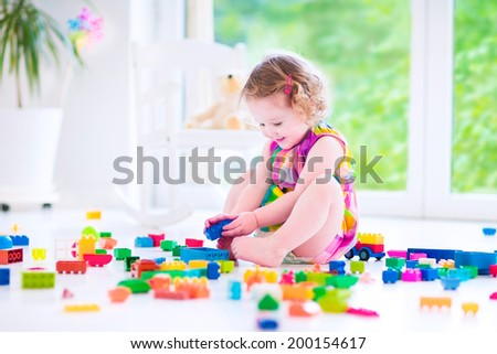Adorable laughing toddler, cute little girl with curly hair wearing a pink summer dress, playing with colorful blocks and toys sitting on a floor in a sunny bedroom with a big window  - stock photo