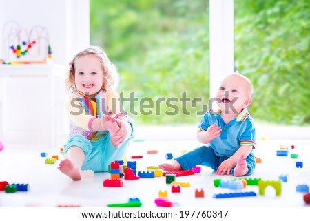Adorable laughing toddler girl and a funny little baby boy, brother and sister, playing with colorful blocks sitting on a floor in a sunny bedroom with a big window  - stock photo