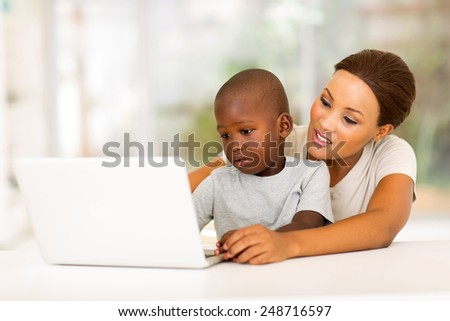 adorable little african boy using laptop with his mother at home - stock photo