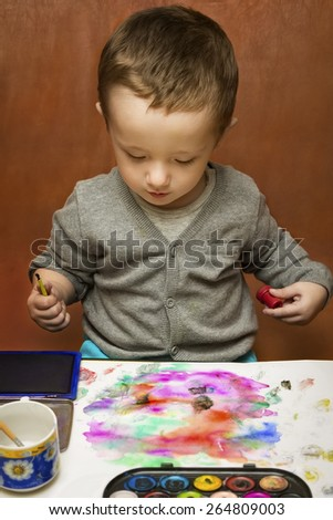 Adorable little baby boy looking concentrated at his painting on a table with watercolors, inkpad and a cup of water, holding a brush and a stamp - stock photo
