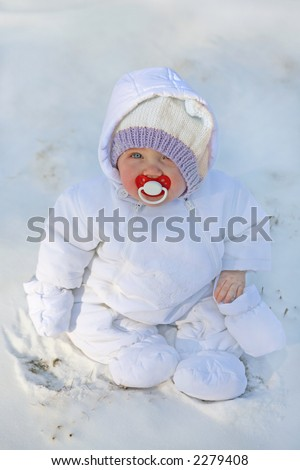 adorable little baby bundled up in white snow suit with a red pacifier - stock photo
