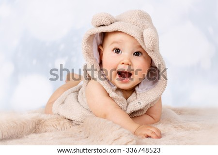Adorable little baby crawling on the floor and wearing hoodie - stock photo