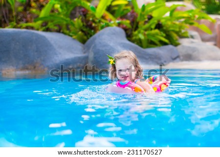 Adorable little baby girl having fun in a swimming pool in a beautiful tropical resort learning to swim playing with colorful inflatable ring - stock photo