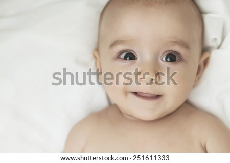 Adorable little baby girl laughing, creeping & playing in the studio, on white background - stock photo