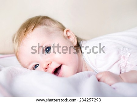 Adorable little baby girl laying in bed. Smiling and looking at the camera. - stock photo