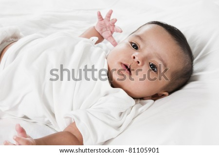 Adorable little baby girl laying in the bed after waking up. Portrait of a smiling new born baby girl - stock photo