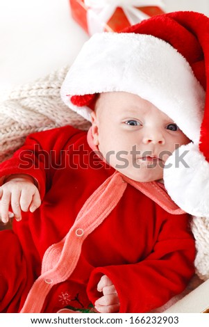 Adorable little baby wearing a santa claus suit and hat lying in straw basket - stock photo