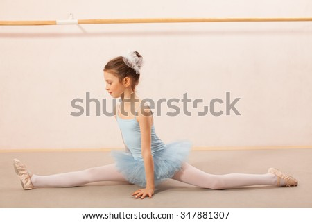 Adorable little ballerina dancer doing the splits pose in ballet studio. She is wearing blue leotard and tutu. - stock photo