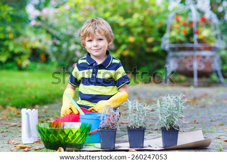Adorable little blond boy gardening and planting flowers in home's garden or farm, on warm sunny day. Outdoors. Environment concept. - stock photo