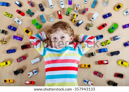 Adorable little blond child playing with lots of toy cars indoor. Kid boy wearing colorful shirt. Happy preschool child having fun at home or nursery. - stock photo