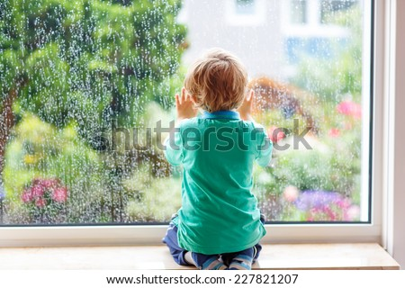 Adorable little blond child sitting near window and looking on raindrops, indoors. - stock photo