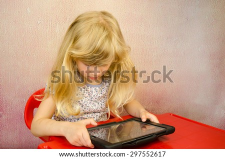 adorable little blond girl holding tablet - stock photo