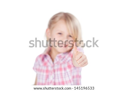 Adorable little blond girl with a beaming smile giving a thumbs up of approval isolated on white with focus to her hand - stock photo