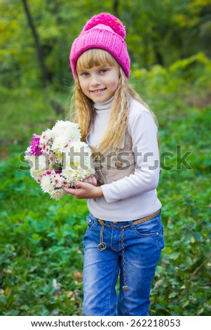 Adorable little blond girl with long blond hair in autumn park. Beautiful little young baby in a pink hat with flowers in their hands - stock photo