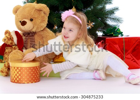 Adorable little blonde girl is sitting near the Christmas tree. Girl stretches hands to a large round box which is a gift. Beside her sits a Teddy bear and stand the box with other gifts. Soon the new - stock photo