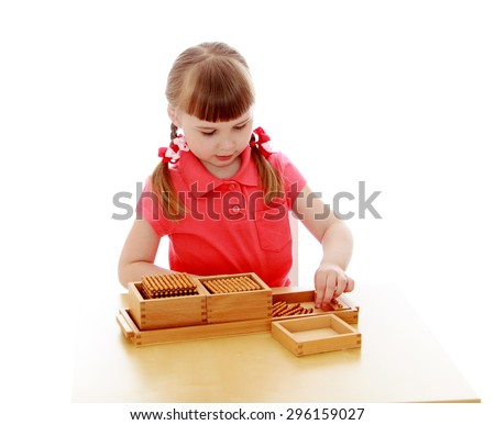 Adorable little blonde girl sitting at table and studying math in a Montessori kindergarten, close-up - isolated on white background - stock photo