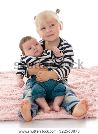 Adorable little blonde girl sitting on the floor and holding his little brother - stock photo