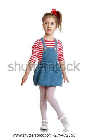 Adorable little blonde girl with braids braided hairstyle in a striped t-shirt and short denim skirt is lifting his leg-Isolated on white background - stock photo