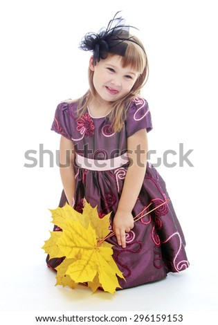 Adorable little blonde girl with long hair and short bangs in long satin dress sits on the floor and holding a yellow maple leaves, autumn mood - isolated on white background - stock photo