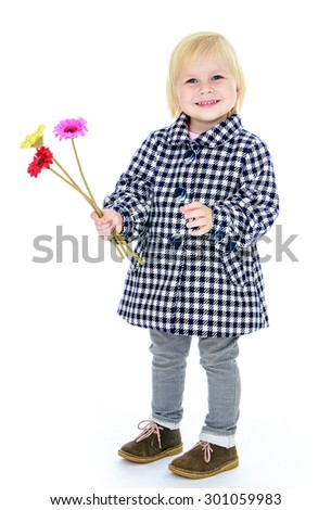 Adorable little blonde girl with short hair in a checkered coat fall. The girl holds a hand a small bunch of flowers and smiling.-Isolated on white background - stock photo