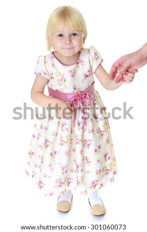 Adorable little blonde girl with short hair in a long flowered dress tied with a pink belt. girl holding her mother's hand and look at the camera-Isolated on white background - stock photo