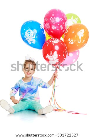 Adorable little blonde girl with the bow on her head sitting on the floor and holding a big bunch of colourful balloons . the girl is very happy and it's her birthday-Isolated on white background - stock photo