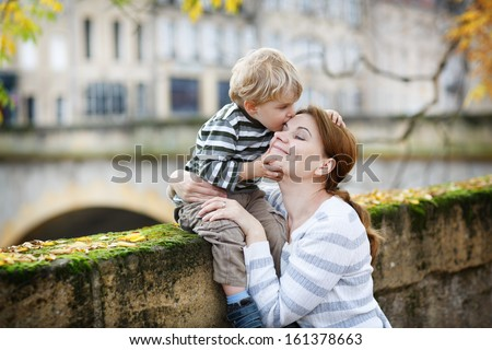 Adorable little boy and mother hugging in autumn city - stock photo