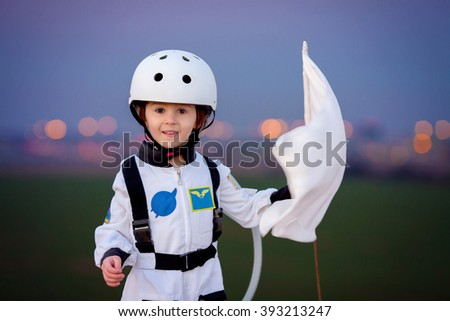Adorable little boy, dressed as astronaut, playing in the park with rocket and flag, dreaming about becoming an astronaut - stock photo