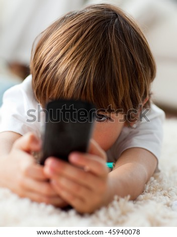 Adorable little boy holding a remote lying on the floor in the living-room - stock photo