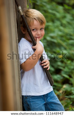 adorable little boy holding a toy rifle and smiling - stock photo