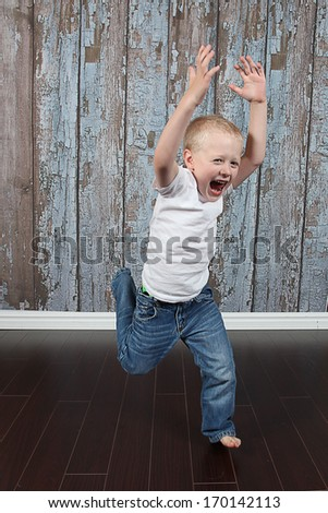 Adorable little boy jumping in studio - stock photo