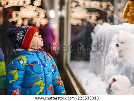 Adorable little boy looking through the display window at Christmas decoration in the shop - stock photo