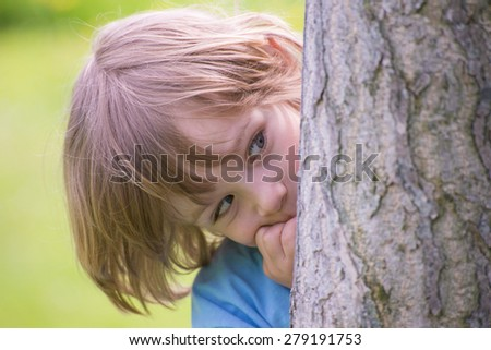 Adorable little boy playing hide and seek hiding behind a  tree trunk in the green summer park - stock photo