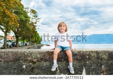 Adorable little boy resting by the lake on a nice summer evening, wearing white shirt, shorts and grey sneakers - stock photo