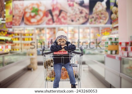 Adorable little boy, sitting in a shopping cart, smiling - stock photo