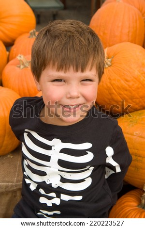 Adorable little boy smiling in a pumpkin patch wearing a skeleton shirt  - stock photo