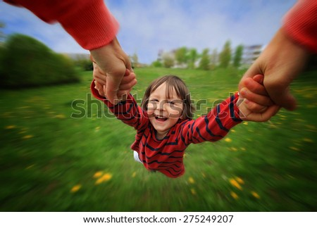 Adorable little boy, spinning in circle in the park, having fun with his mom, laughing, wide angle view - stock photo