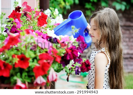 Adorable little brunette kid girl watering flowers at the sunny summer day - stock photo