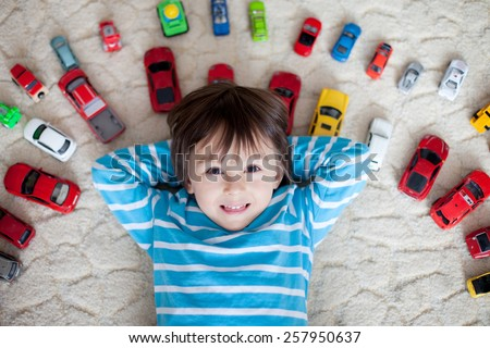 Adorable little caucasian boy in white and blue striped shirt, lying on the ground, red, yellow, blue and white toy cars around him , looking and smiling at the camera, shot from above - stock photo