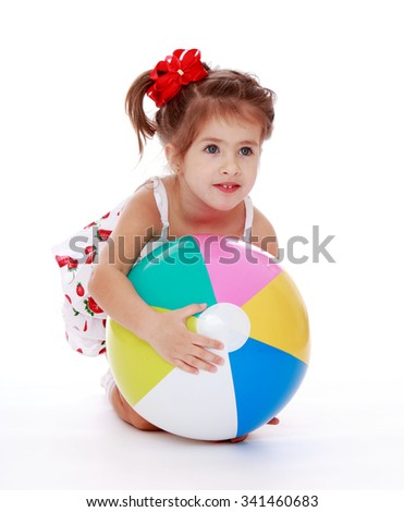 Adorable little Caucasian girl with the ponytail on the head in which braided red bow hugging the big, colorful bouncy ball.-Isolated on white background - stock photo