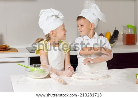 Adorable Little Chefs Very Happy Playing at Kitchen Area - stock photo