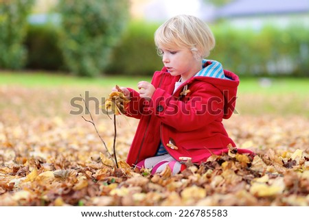 Adorable little child, blonde toddler girl in warm red duffle coat, playing with leaves in autumn park - stock photo