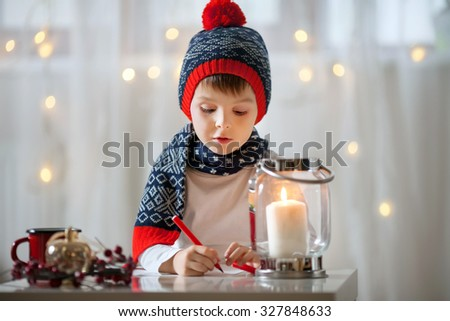 Adorable little child, boy, writing letter to Santa - stock photo
