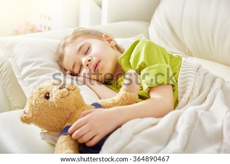 Adorable little child girl sleeping in the bed with her toy. The child girl hugs the teddy bear. - stock photo