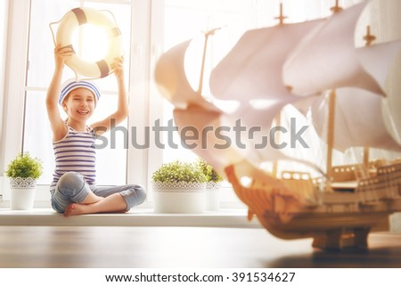 Adorable little child sitting on the window. Girl dreams of sea, adventures and travel. Girl has a toy ship. - stock photo