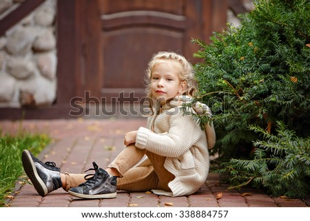 Adorable little curly blond girl in beige knitted sweater smiling sitting on a background of green fur-trees and house in autumn - stock photo