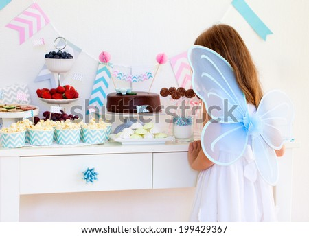 Adorable little fairy girl with wings on a birthday party near dessert table - stock photo