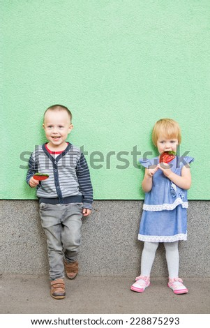 Adorable little girl and boy with colorful lollipops - stock photo